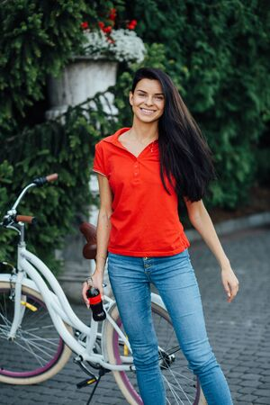 Beautiful smiling girl in a red T-shirt with water in her hands stands near the bike