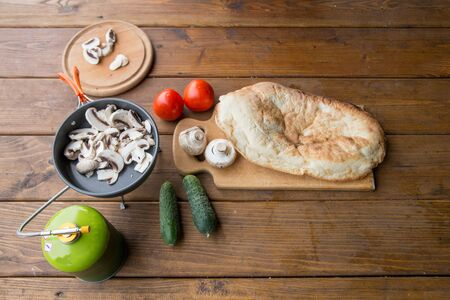 a variety of vegetables, cucumbers, tomatoes, mushrooms and pita for cooking dinner in nature at the campsite