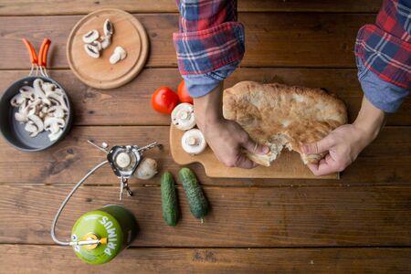 man breaks pita bread with his hands on a picnic at the campsite Archivio Fotografico