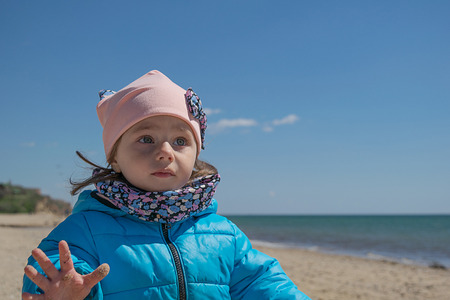 Little white girl concentrates on the sky on the beach in spring