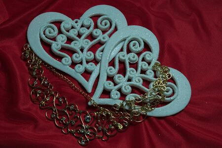luxury house: two beautiful openwork carved white hearts on a red background and a gold necklace with precious stones