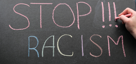 adds: An inscription of stop racism with a multi-colored chalk on a slate in a blue frame and a hand with chalk that adds it Stock Photo