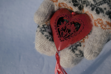 only 1 woman: Hands in mittens holding red heart with two cupids in the winter on snow background