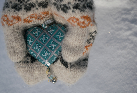 Vintage blue heart in his hands in the mittens on a background of white snow