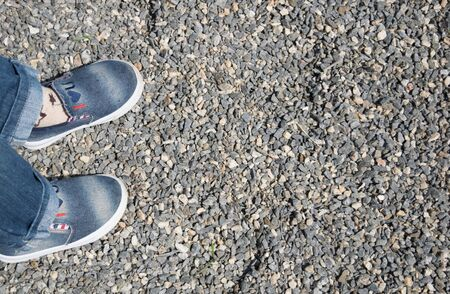 Background of small gravel and baby legs in jeans and denim slips on the right