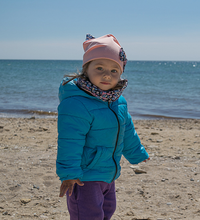 Portrait of a small two-year-old white girl on the beach