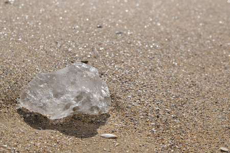 piece of clear ice on a beach in the sand