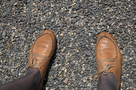 Female feet in brown leather shoes and kapron pantyhose of mocha color on a background of fine gravel
