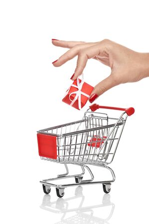 Woman hand putting down christmas present into shopping trolley isolated on white. Conceptual image - buying christmas presents. Zdjęcie Seryjne