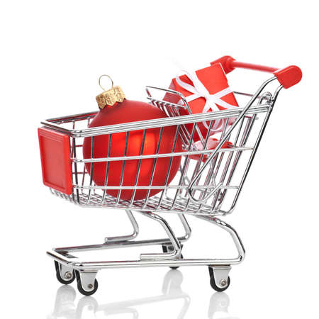 Shopping trolley with gift box and red christmas ball isolated on white background, with reflection. Stock Photo - 11509568