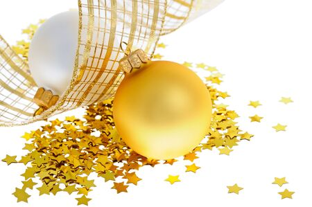 Two christmas balls on heap of confetti stars with yellow ribbon Stock Photo - 11509570