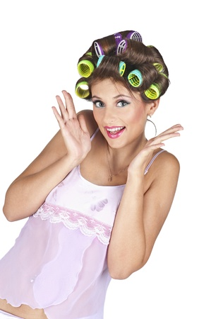 Portrait of young woman with hair-curlers - isolated on white background. Positive expression, hands near the face.