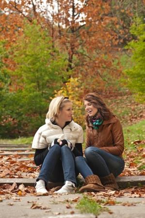 amigas conversando: Jóvenes muchachas bonitas risa en el parque de otoño