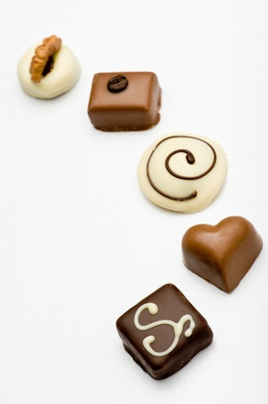 Delicious dark, milk, and white chocolate sweets on white background.