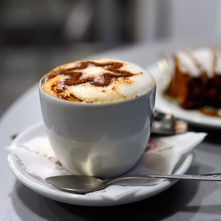 creamy: Cup of coffee and cake in cafe, shallow DOF
