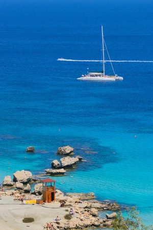 Catamaran anchoring at coastline  photo