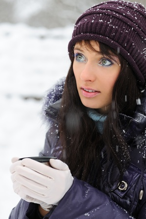 mulled wine: Portrait of the beautiful girl drinking hot beverage in snowy winter.
