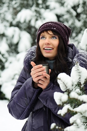 mulled: Portrait of the beautiful girl drinking hot beverage in snowy winter.