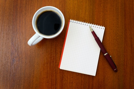 Pencil on a white spiral squared notebook with cup of coffee viewed from above