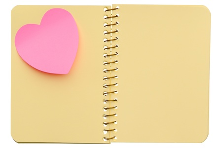 Open spiral notebook with post-it note in shape of heart isolated on white background photo