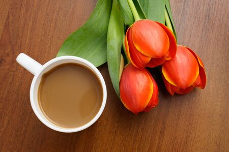 White cup of coffee with red tulips on wooden table  photo