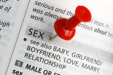 Red push pin near the word SEX on a dictionary page