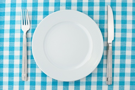 Empty dinner plate with fork and knife on blue and white checked gingham tablecloth