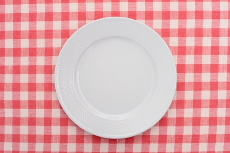 Empty dinner plate on red and white checked gingham tablecloth   photo