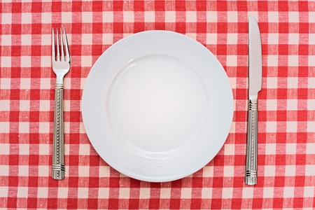 Empty dinner plate with fork and knife on red and white checked gingham tablecloth photo