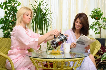 Two smiling girls have morning tea in the kitchen   Stock Photo - 11706679