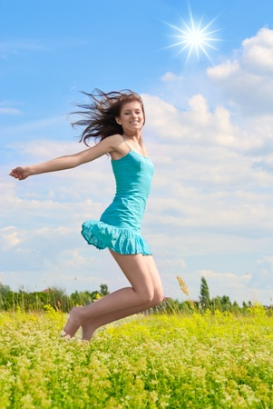 Happy girl jumping in the sky and laughing.  photo