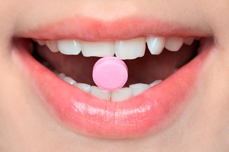 Close-up of pink pill in woman's mouth 스톡 콘텐츠