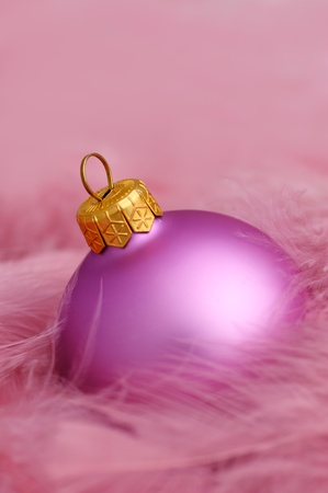 Bright purple christmas bulb with purple feathers photo