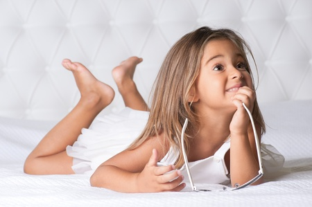 little girl barefoot: Portrait of cute girl with eyewear lying barefoot in the bed Stock Photo