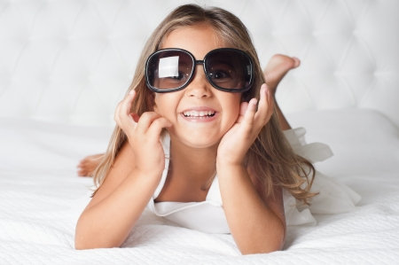 Portrait of cute girl with eyewear lying barefoot in the bed photo