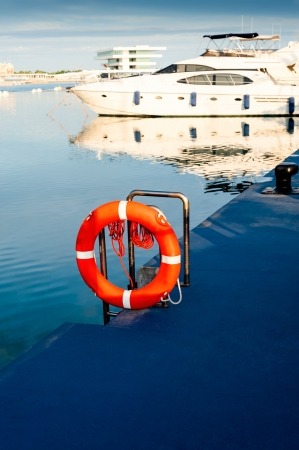 life buoy: Lifebuoy with yacht on the background  Photo taken in port of Valencia, Spain  Stock Photo