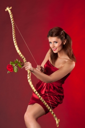 Young woman with bow and red rose as arrow on red background   Concept for Valentine photo