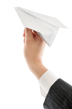 throw paper: Mans hand launching white paper airplane isolated on white background. Stock Photo