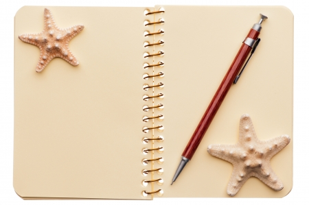 Yellow notebook with pen and two starfishes isolated on white background. photo