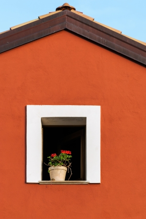 attic window: Attic window with geranium in the pot. Red rural house in Cilento area, Campania, Italy. Stock Photo