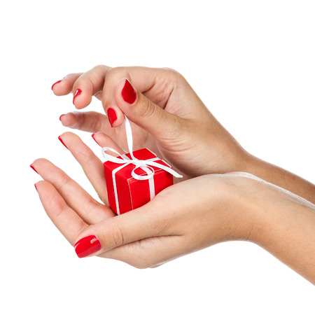 christmas manicure: Woman hand with gift isolated on white background. Conceptual image - buying presents.