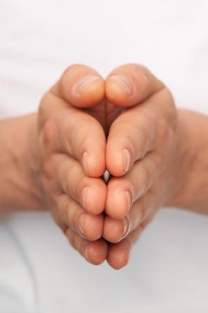 folded hands: Mans hands folded over white body background.