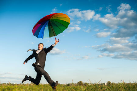 Businessman running in a green field with multicolored umbrella. photo