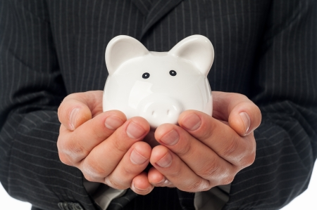 retirement fund: Man holding white piggy bank over black suit background  Stock Photo