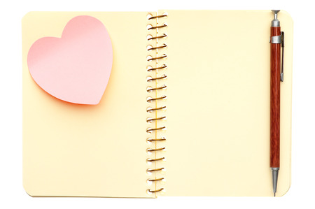 Opened spiral notebook with post-it note in shape of heart and pen isolated on white background photo