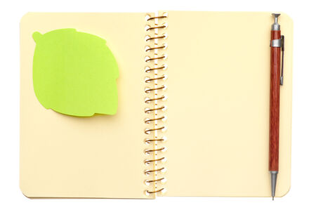 Opened spiral notebook with post-it note in shape of leaf and a pen isolated on white background photo