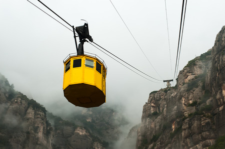 cableway: Photo of yellow cable car taken during autumn foggy day.