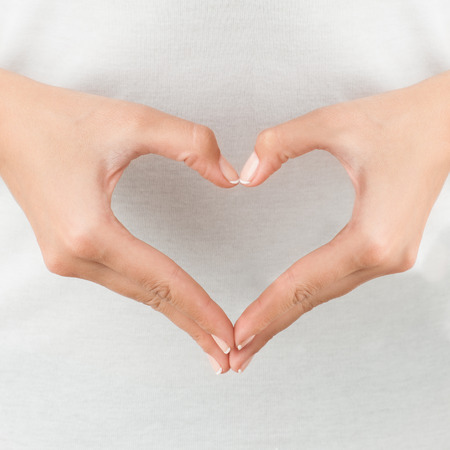 body heart: The form of heart shaped by female hands on body background isolated on white. Stock Photo