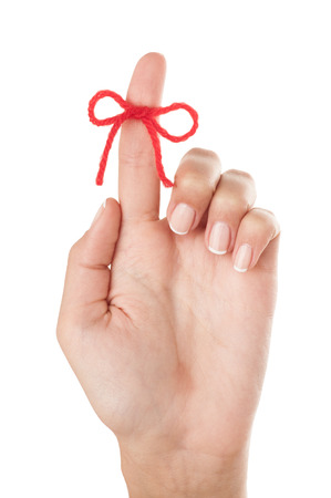 Red bow on finger isolated on white background. photo
