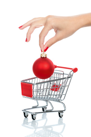 Woman hand putting down christmas ball into shopping trolley isolated on white. Conceptual image - buying christmas balls. photo
